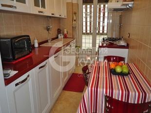 Белая прямая кухня с красной столешницей